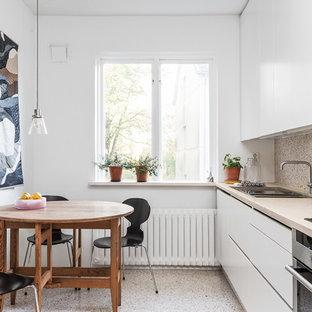 Foto på ett mellanstort skandinaviskt linjärt kök och matrum, med en dubbel diskho, vita skåp, träbänkskiva, rostfria vitvaror, terrazzogolv och släta luckor