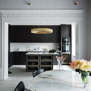 Bild på ett stort funkis kök, med en enkel diskho, släta luckor, svarta skåp, marmorbänkskiva, svarta vitvaror, ljust trägolv och en köksö
