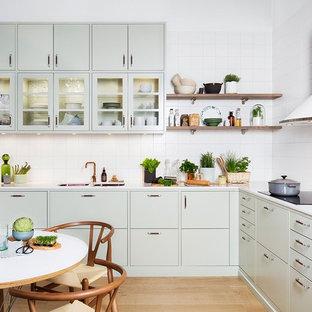 Foto på ett mellanstort nordiskt kök, med en dubbel diskho, släta luckor, gröna skåp, vitt stänkskydd, ljust trägolv, marmorbänkskiva och stänkskydd i porslinskakel