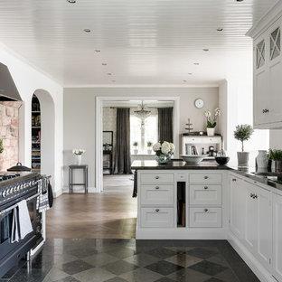 Lantlig inredning av ett stort kök, med en dubbel diskho, luckor med infälld panel, vita skåp, svarta vitvaror, en halv köksö, marmorbänkskiva och stänkskydd med metallisk yta