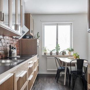 Foto på ett skandinaviskt svart kök, med en dubbel diskho, luckor med glaspanel, skåp i ljust trä, vitt stänkskydd och mörkt trägolv