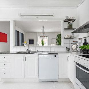 Inredning av ett minimalistiskt litet kök, med vita skåp, bänkskiva i rostfritt stål, vitt stänkskydd, stänkskydd i porslinskakel, vita vitvaror, målat trägolv och vitt golv