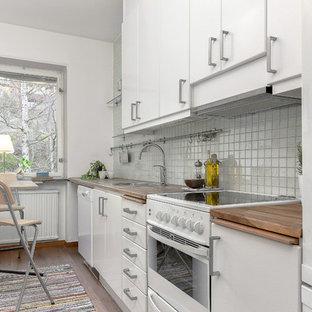 Idéer för ett litet skandinaviskt linjärt kök, med en enkel diskho, släta luckor, vita skåp, träbänkskiva, vitt stänkskydd, vita vitvaror, mellanmörkt trägolv och stänkskydd i keramik