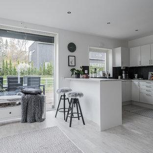 Bild på ett mellanstort nordiskt kök, med släta luckor, vita skåp, svart stänkskydd, en halv köksö, grått golv, rostfria vitvaror och ljust trägolv