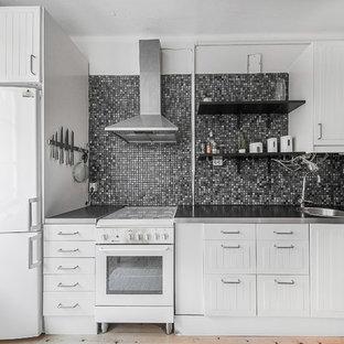Bild på ett litet minimalistiskt linjärt kök, med vita skåp och bänkskiva i rostfritt stål