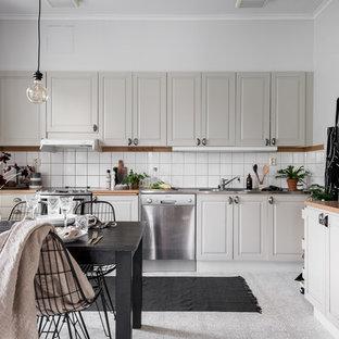 Idéer för att renovera ett mellanstort minimalistiskt kök, med en integrerad diskho, luckor med upphöjd panel, grå skåp, vitt stänkskydd, rostfria vitvaror och träbänkskiva