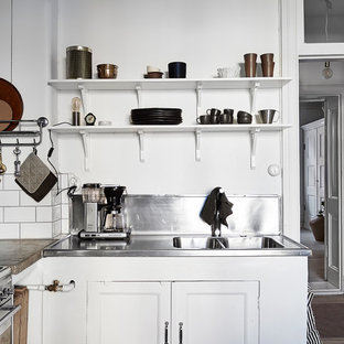 Small scandinavian enclosed kitchen ideas - Example of a small danish l-shaped enclosed kitchen design in Gothenburg with recessed-panel cabinets, white cabinets, stainless steel countertops and no island