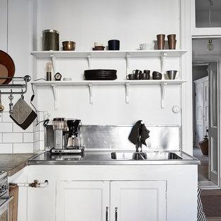 Bild på ett avskilt, litet skandinaviskt l-kök, med luckor med infälld panel, vita skåp och bänkskiva i rostfritt stål