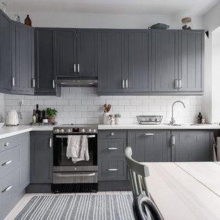 Exempel på ett mellanstort nordiskt kök, med en nedsänkt diskho, luckor med profilerade fronter, grå skåp, laminatbänkskiva, vitt stänkskydd, stänkskydd i keramik, svarta vitvaror, ljust trägolv och vitt golv