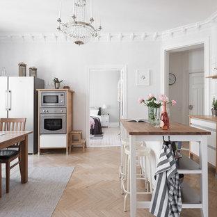 Bild på ett mellanstort minimalistiskt kök och matrum, med öppna hyllor, träbänkskiva, vitt stänkskydd, stänkskydd i porslinskakel, en köksö, rostfria vitvaror, ljust trägolv och beiget golv