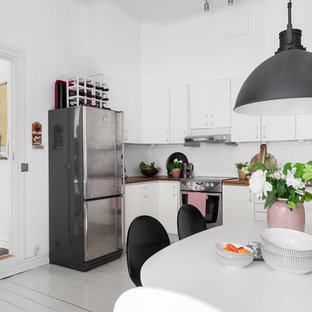 Mid-sized scandinavian eat-in kitchen appliance - Inspiration for a mid-sized scandinavian single-wall painted wood floor and gray floor eat-in kitchen remodel in Gothenburg with a drop-in sink, flat-panel cabinets, white cabinets, wood countertops, white backsplash, glass sheet backsplash, stainless steel appliances and no island