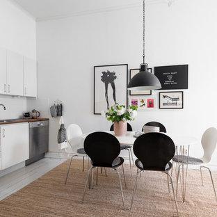 Idéer för ett mellanstort minimalistiskt linjärt kök och matrum, med en nedsänkt diskho, släta luckor, vita skåp, träbänkskiva, vitt stänkskydd, glaspanel som stänkskydd, rostfria vitvaror, målat trägolv och grått golv