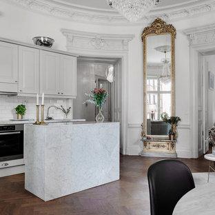 Foto på ett vintage kök, med luckor med upphöjd panel, grå skåp, vitt stänkskydd, stänkskydd i tunnelbanekakel, rostfria vitvaror, mörkt trägolv, en köksö och brunt golv