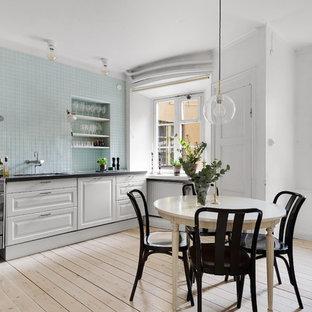 Inspiration för ett stort skandinaviskt svart svart kök och matrum, med vita skåp, blått stänkskydd, stänkskydd i glaskakel, ljust trägolv, beiget golv, en undermonterad diskho, luckor med upphöjd panel och rostfria vitvaror