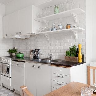 Foto på ett mellanstort nordiskt brun linjärt kök och matrum, med en dubbel diskho, vita skåp, vitt stänkskydd, stänkskydd i porslinskakel, vita vitvaror, målat trägolv, vitt golv och släta luckor