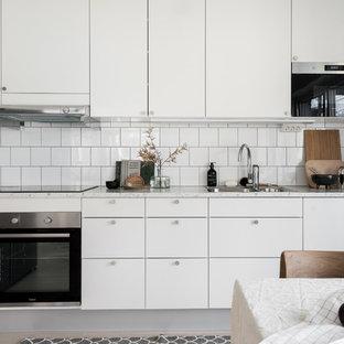 Idéer för att renovera ett mellanstort minimalistiskt grå grått kök, med en nedsänkt diskho, släta luckor, vita skåp, laminatbänkskiva, vitt stänkskydd, stänkskydd i keramik, rostfria vitvaror och ljust trägolv