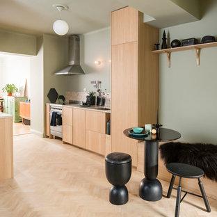 Inredning av ett nordiskt litet beige beige kök, med skåp i ljust trä, granitbänkskiva, ljust trägolv, beiget golv, en undermonterad diskho, släta luckor, beige stänkskydd, stänkskydd i sten och rostfria vitvaror