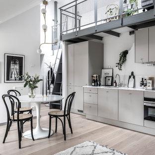 Idéer för ett mellanstort industriellt linjärt kök och matrum, med en enkel diskho, släta luckor, grå skåp, marmorbänkskiva och ljust trägolv