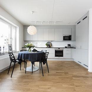 Idéer för att renovera ett minimalistiskt svart svart kök, med släta luckor, vita skåp, vitt stänkskydd, svarta vitvaror, mellanmörkt trägolv och brunt golv