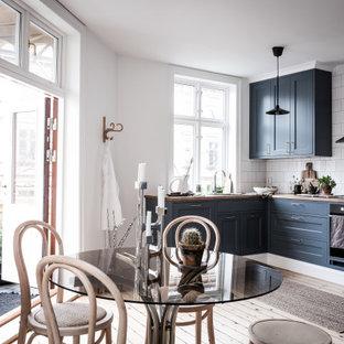Skandinavisk inredning av ett brun brunt kök, med skåp i shakerstil, blå skåp, träbänkskiva, vitt stänkskydd, rostfria vitvaror, ljust trägolv och beiget golv