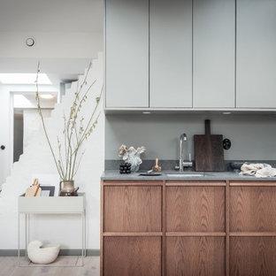 Idéer för att renovera ett mellanstort skandinaviskt grå grått kök, med en undermonterad diskho, släta luckor, skåp i mellenmörkt trä och beiget golv