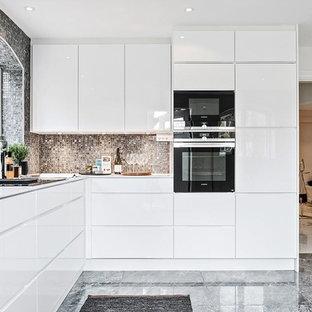 Bild på ett avskilt, mellanstort funkis l-kök, med släta luckor, vita skåp, grått golv, marmorgolv, grått stänkskydd och svarta vitvaror