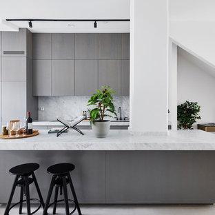 Exempel på ett minimalistiskt linjärt kök med öppen planlösning, med en undermonterad diskho, släta luckor, grå skåp, grått stänkskydd, en köksö och beiget golv