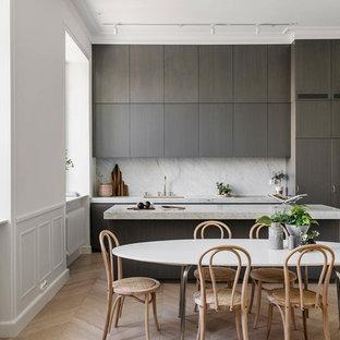 Bild på ett minimalistiskt grå linjärt grått kök och matrum, med en undermonterad diskho, släta luckor, grå skåp, grått stänkskydd, ljust trägolv, en köksö och beiget golv