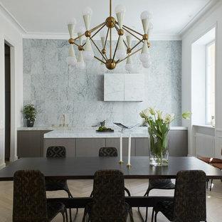 Inredning av ett modernt grå linjärt grått kök med öppen planlösning, med en undermonterad diskho, släta luckor, grå skåp, grått stänkskydd, ljust trägolv, en köksö och brunt golv