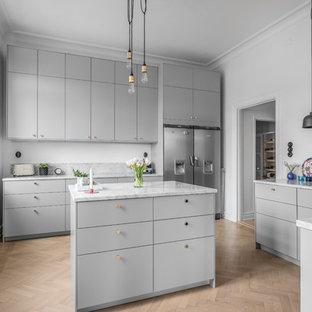 Inredning av ett nordiskt avskilt, stort grå grått u-kök, med en enkel diskho, släta luckor, grå skåp, marmorbänkskiva, grått stänkskydd, stänkskydd i marmor, rostfria vitvaror, ljust trägolv, en köksö och beiget golv