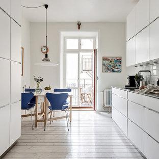 Idéer för ett mellanstort minimalistiskt kök, med släta luckor, vita skåp, bänkskiva i rostfritt stål, stänkskydd i porslinskakel, integrerade vitvaror, ljust trägolv, beiget golv och vitt stänkskydd