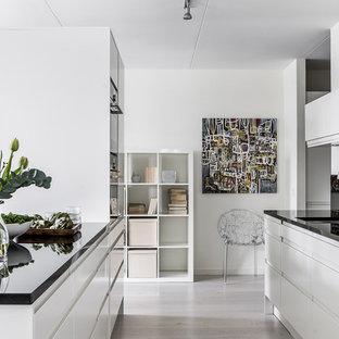 Inspiration för stora moderna kök, med en undermonterad diskho, släta luckor, vita skåp, svart stänkskydd, svarta vitvaror, ljust trägolv och en köksö
