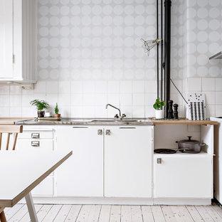 На фото: линейные кухни в скандинавском стиле с белыми фасадами и столешницей из дерева