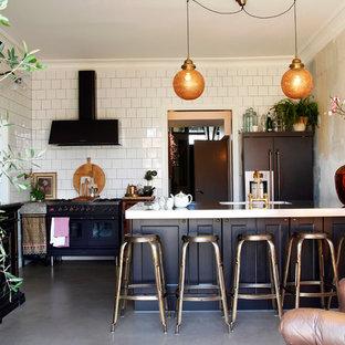 マルメの大きいエクレクティックスタイルのおしゃれなキッチン (ドロップインシンク、落し込みパネル扉のキャビネット、黒いキャビネット、黒い調理設備、コンクリートの床) の写真