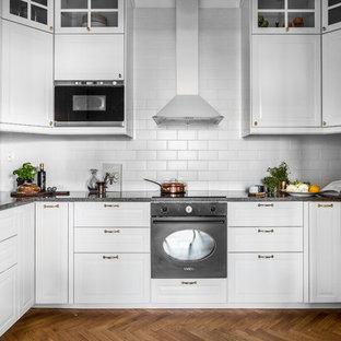 Inredning av ett minimalistiskt mellanstort grå grått u-kök, med vita skåp, en undermonterad diskho, luckor med upphöjd panel, vitt stänkskydd, stänkskydd i tunnelbanekakel, integrerade vitvaror, mörkt trägolv och brunt golv