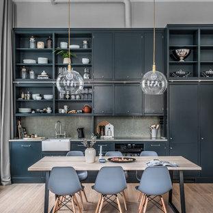 Modern inredning av ett grå linjärt grått kök, med en rustik diskho, släta luckor, svarta skåp, grått stänkskydd, integrerade vitvaror, mörkt trägolv och brunt golv