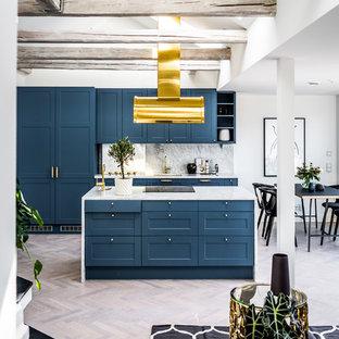 Bild på ett funkis kök med öppen planlösning, med blå skåp, marmorbänkskiva, vitt stänkskydd, stänkskydd i marmor, integrerade vitvaror, ljust trägolv, en köksö och skåp i shakerstil