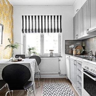 Exempel på ett nordiskt kök och matrum, med en dubbel diskho, grå skåp, grått stänkskydd, vita vitvaror, mörkt trägolv och brunt golv