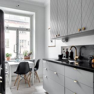 Bild på ett mellanstort minimalistiskt linjärt kök, med luckor med profilerade fronter, grå skåp, granitbänkskiva, en enkel diskho, grått stänkskydd och ljust trägolv