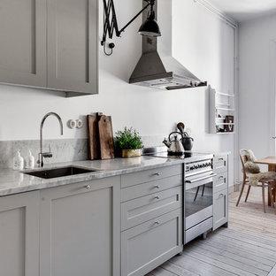 Inredning av ett minimalistiskt avskilt, mellanstort linjärt kök, med en nedsänkt diskho, luckor med upphöjd panel, grå skåp, marmorbänkskiva, rostfria vitvaror och ljust trägolv