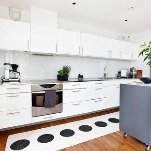 Idéer för ett avskilt, mellanstort modernt linjärt kök, med släta luckor, vita skåp, rostfria vitvaror, en dubbel diskho, bänkskiva i rostfritt stål, mellanmörkt trägolv och en köksö