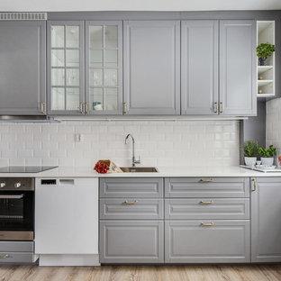 Exempel på ett stort nordiskt linjärt kök, med en enkel diskho, luckor med upphöjd panel, grå skåp, vitt stänkskydd, stänkskydd i keramik, rostfria vitvaror och ljust trägolv