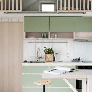 Skandinavisk inredning av ett beige linjärt beige kök, med en halv köksö, en nedsänkt diskho, släta luckor, gröna skåp, träbänkskiva och vitt stänkskydd