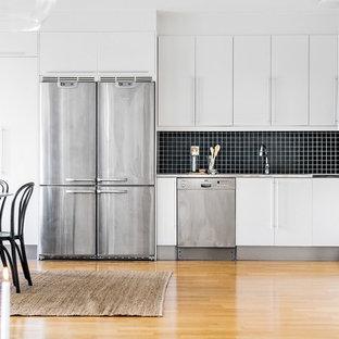 Inspiration för ett stort skandinaviskt kök, med släta luckor, vita skåp, svart stänkskydd, rostfria vitvaror och mellanmörkt trägolv