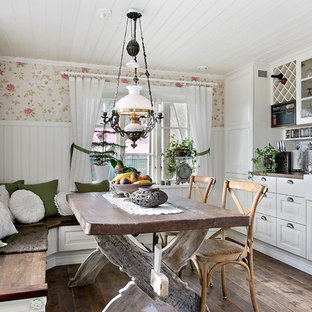 Photo of a country l-shaped eat-in kitchen in Gothenburg with a farmhouse sink, raised-panel cabinets, white cabinets, white splashback, subway tile splashback, medium hardwood floors, a peninsula and brown floor.