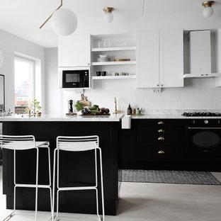 Inredning av ett modernt grå grått kök, med släta luckor, svarta skåp, vitt stänkskydd, stänkskydd i tunnelbanekakel, integrerade vitvaror, ljust trägolv, en köksö och grått golv