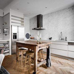 Exempel på ett minimalistiskt linjärt kök, med marmorbänkskiva, rostfria vitvaror, mellanmörkt trägolv och en köksö