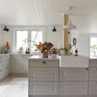 Lantlig inredning av ett vit vitt l-kök, med en rustik diskho, luckor med upphöjd panel, grå skåp, ljust trägolv, en köksö och beiget golv