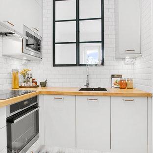 Inredning av ett nordiskt litet l-kök, med en nedsänkt diskho, släta luckor, vita skåp, träbänkskiva, vitt stänkskydd, stänkskydd i tunnelbanekakel, rostfria vitvaror och klinkergolv i keramik