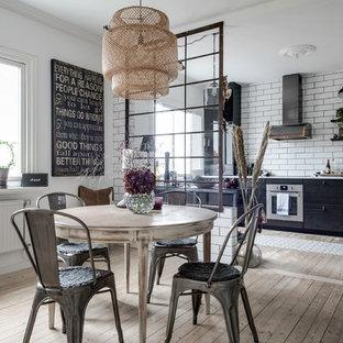 Skandinavisk inredning av ett vit linjärt vitt kök och matrum, med en rustik diskho, släta luckor, svarta skåp, vitt stänkskydd, stänkskydd i tunnelbanekakel, rostfria vitvaror, ljust trägolv och beiget golv